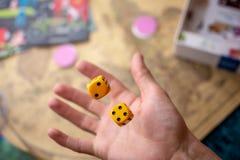 La main jette les matrices jaunes sur le terrain de jeu Chance et excitation Jeux de société de concept photos stock