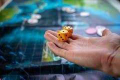 La main jette les matrices jaunes sur le terrain de jeu Chance et excitation Jeux de soci?t? Moments de jeu dans la dynamique photo libre de droits