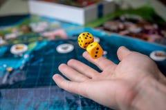 La main jette les matrices jaunes sur le terrain de jeu Chance et excitation Jeux de soci?t? Moments de jeu dans la dynamique image stock
