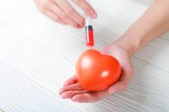 La main jugeant en plastique avec la seringue complètent le coeur Photos libres de droits