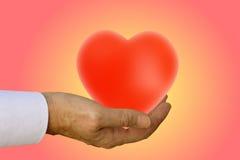 La main mûre offre le coeur Images stock