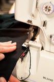 La main manipule le tissu noir sur le serger Images stock