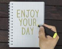 La main masculine écrit apprécient votre jour sur un bloc-notes Photo stock