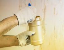 La main masculine a appliqué la peinture décorative sur le mur avec le sable Photographie stock libre de droits