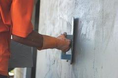 La main masculine asiatique d'entrepreneur en bâtiments portant le gant orange lissant le mortier s'est appliquée sur un mur exté images libres de droits