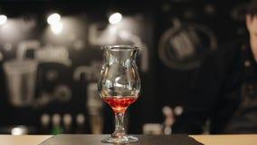 La main masculine de barman verse le sirop rouge et met les feuilles en bon état dans un verre vide sur un compteur de barre banque de vidéos