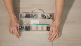 La main masculine ouvre la boîte pour des écrous, boulons, vis banque de vidéos
