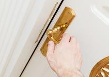 La main masculine ouvre la porte blanche avec la poignée d'or Photo stock