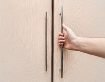 La main masculine sont ouverte les portes de placard, bois léger Image stock