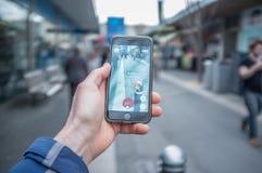 La main masculine tenant l'iPhone 6 avec Pokemon vont sur une rue passante photos libres de droits