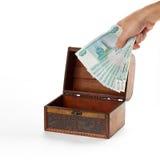 La main met l'argent russe dans le coffre pour le dépôt roubles Photo stock