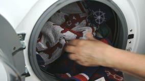 La main met la serviette à l'intérieur du tambour en acier de machine à laver banque de vidéos