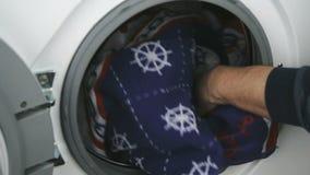 La main met la serviette à l'intérieur du tambour en acier de machine à laver clips vidéos