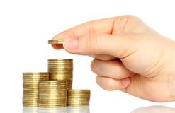 La main a mis des pièces de monnaie à la pile de pièces de monnaie Photographie stock