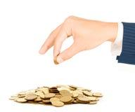 La main a mis des pièces de monnaie à la pile de pièces de monnaie Images libres de droits