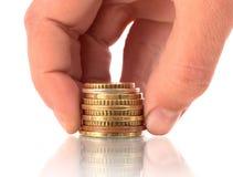 La main a mis des pièces de monnaie à la pile de pièces de monnaie Image stock