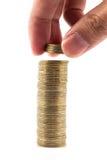 La main a mis des pièces de monnaie à la pile de pièces de monnaie sur le fond blanc image libre de droits