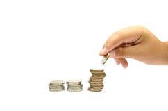 La main a mis des pièces de monnaie à la pile de pièces de monnaie Photo libre de droits
