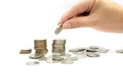 La main a mis des pièces de monnaie à la pile de pièces de monnaie Images stock