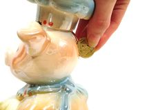 La main a mis l'argent à la banque en céramique porcine pour l'argent au-dessus du backgr blanc photo stock