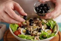 La main a mis l'olive dans la cuvette avec les légumes frais et la conserve de thon photos libres de droits