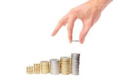 La main a mis la pièce de monnaie à l'escalier d'argent Images stock