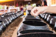 La main a mis la pièce de monnaie dans la petite aumône roulent, croyance de qualité dans le bouddhiste photos stock