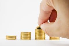 La main a mis la pièce d'or sur la pile de pièces de monnaie Images stock