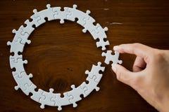 La main a mis le dernier morceau de puzzle denteux pour accomplir la mission, les solutions d'affaires, le succès et le concept d images libres de droits
