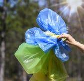 La main montre les sacs en polyéthylène multicolores vides pour des déchets images stock
