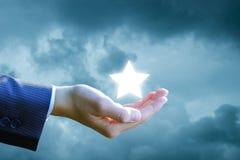 La main montre une étoile dans le ciel Photo stock