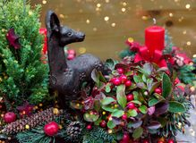 La main a ouvré la composition florale botanique en beau Noël de la bougie verte fraîche de renne de gui de baie de houx de branc photographie stock