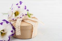 La main a ouvré le cadeau et les fleurs Photographie stock libre de droits