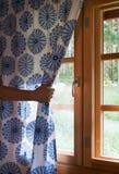 La main ouvre le rideau sur la fenêtre en bois de maison de cottage La lumière du soleil lumineuse brille  Belle lumière de matin Photos stock