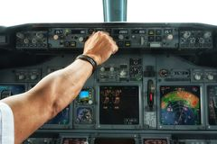 La main pilote actionnent un commutateur sur des panneaux d'aéronefs Photos stock