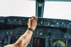 La main pilote actionnent un commutateur sur des panneaux d'aéronefs Photo stock