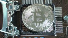 La main place la devise virtuelle argentée de Bitcoin sur une unité centrale de traitement de carte mère à la place clips vidéos