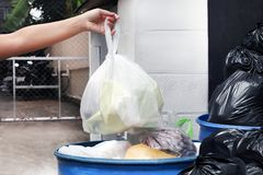 La main porte les sacs de déchets en plastique de rebut et en allant vider des déchets dans la poubelle, remettez tient les sacs  photos libres de droits