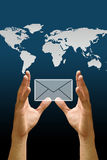 La main portent le graphisme d'email avec la carte du monde Photo stock