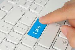 La main poussant le bleu aiment le bouton Photographie stock