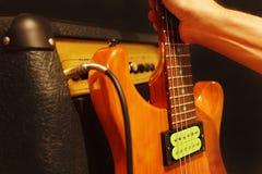 La main prend la guitare électrique se penchant contre l'amplificateur sur le fond noir images stock