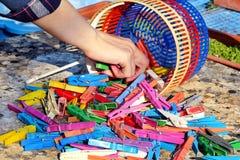 La main prend le support coloré de pinces à linge sur la table dans le jardin Images libres de droits