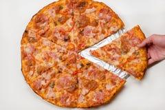 La main prend une tranche de pizza Images stock