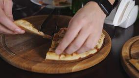 La main prennent un morceau de grande pizza italienne L'homme mange de la pizza en café avec des amis Il prend une tranche, le mo banque de vidéos