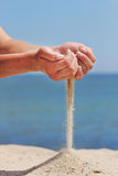 La main projette le sable Photographie stock