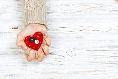 La main qui a serré la table en bois de hearton rouge Concept d'amour avec le copyspace Image stock