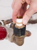 La main réparant une tuyauterie siffle Photographie stock libre de droits