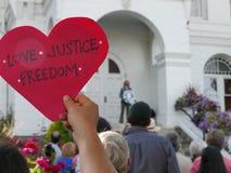 La main retardent le signe en forme de coeur de LIBERTÉ de JUSTICE d'AMOUR de ` Photos stock