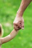 La main retient la main un enfant de parent Photo libre de droits