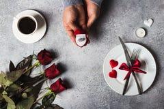 La main romantique d'homme d'arrangement de table de dîner de jour de valentines tenant la bague de fiançailles dans la boîte m'é Image libre de droits